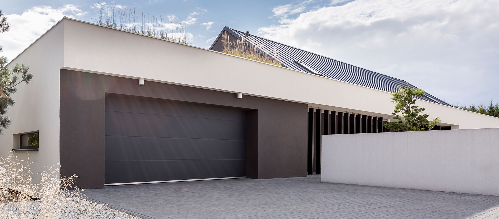 Modern luxurious house with huge garage and tree next to building